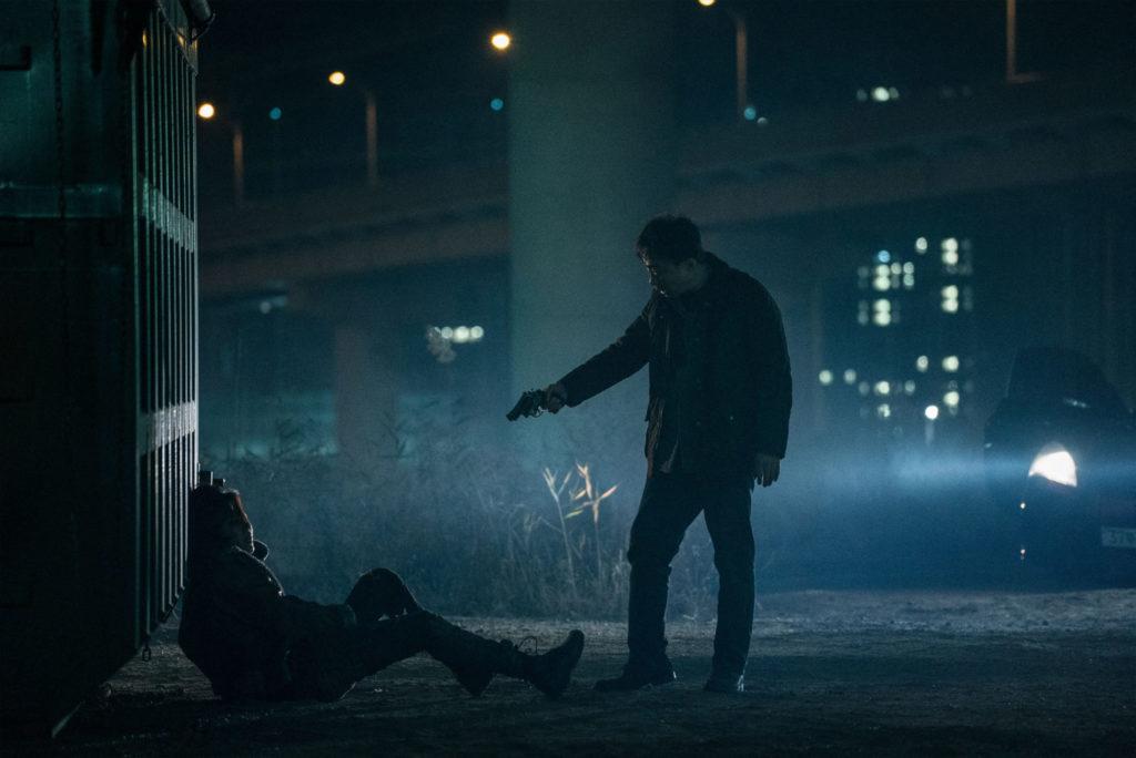 """In """"The Beast"""" bedroht Jeong Han-Soo (Lee Sung-Min) einen unbekannten Mann vor einem Container in der Dunkelheit mit seinem Revolver"""