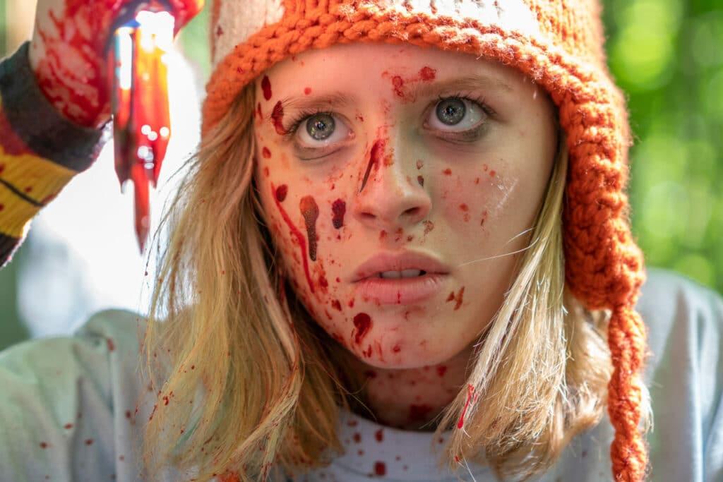 Becky mit Mütze und blutverschmierten Gesicht mit bluttriefenden Bleistiften in der Hand