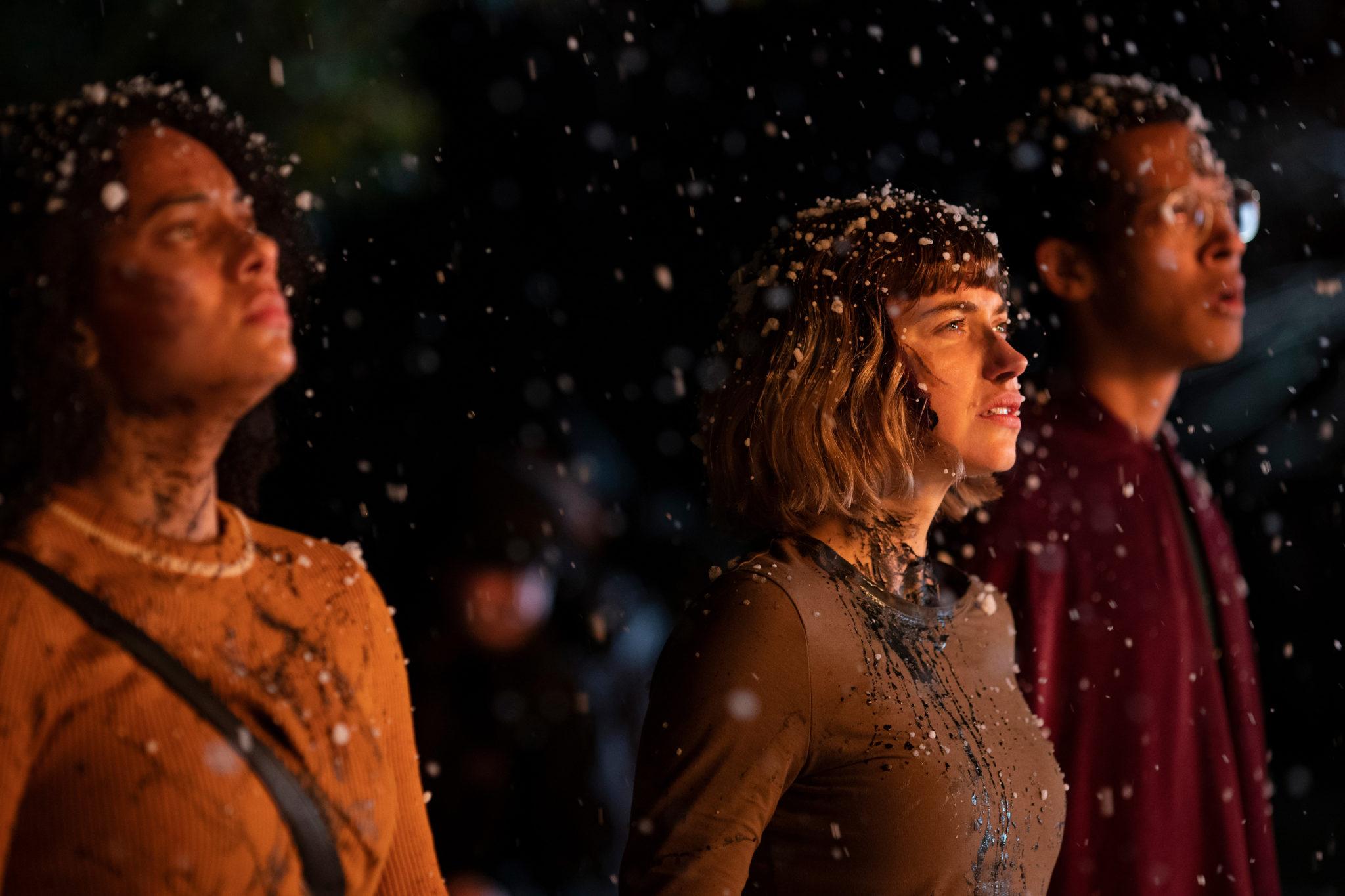 Kirs (links), Riley (mitte) und Landon (rechts) stehen blutverschmiert im Schnee und beobachten etwas. Sie werden hell durch eine Lichtquelle beleuchtet.