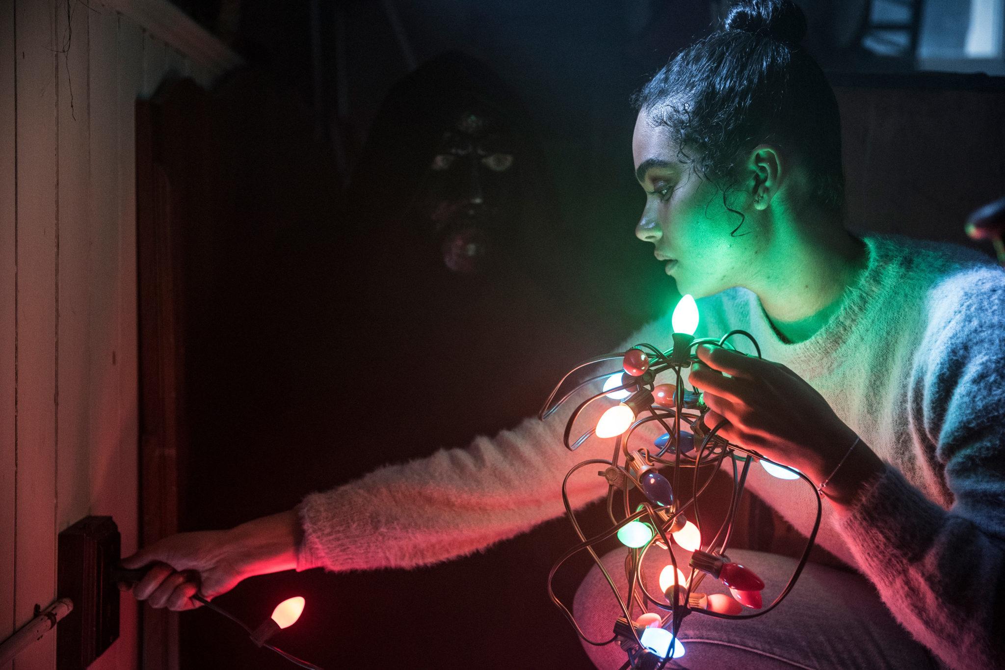 Jesse versucht Weihnachtslichter zu überprüfen. Die verschiedenfarbige Lichtquelle entblößt einen maskierten Unbekannten im Hintergrund in Black Christmas 2019