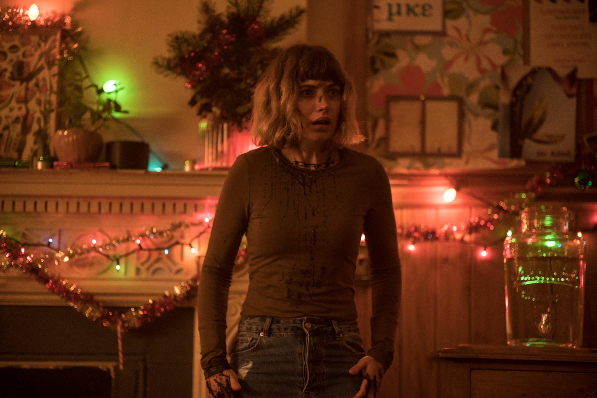 Vor einem weihnachtlich geschmückten Hintergrund steht Riley. Sie beobachtet etwas schockiert und ist dabei mit Blutflecken übersät in Black Christmas 2019