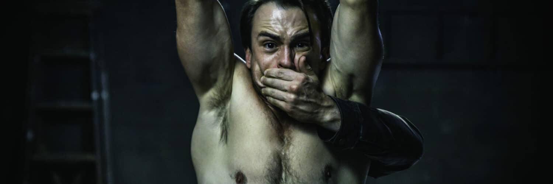 Der Hauptdarsteller von Bloody Hell steht oberkörperfrei vor der Kamera, reckt die Hände in die Höhe und bekommt von einer unbekannten Person den Mund zugehalten