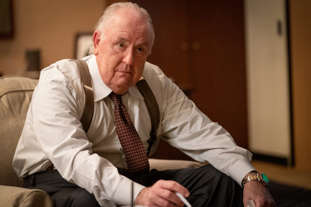 John Lithgow als Roger Ailes sitzt aufrecht in einem Sessel in seinem Büro