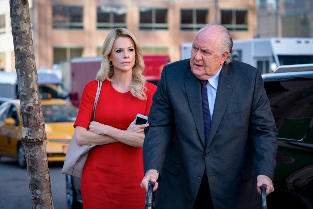 Szene aus Bombshell: Charlize Theron als Megyn Kelly steht neben Roger Ailes, gespielt von John Lithgow, vor dessen Auto auf der Straße