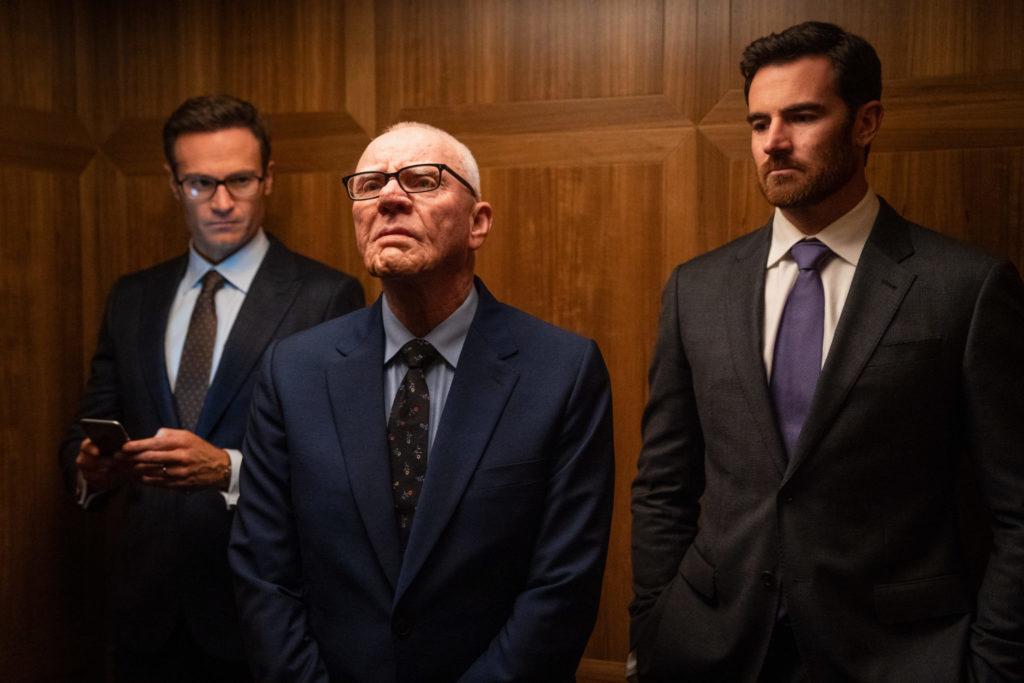 Szene aus Bombshell - Das Ende des Schweigens: Malcolm McDowell als Rupert Murdoch steht mit seinen Söhnen im Film im Aufzug