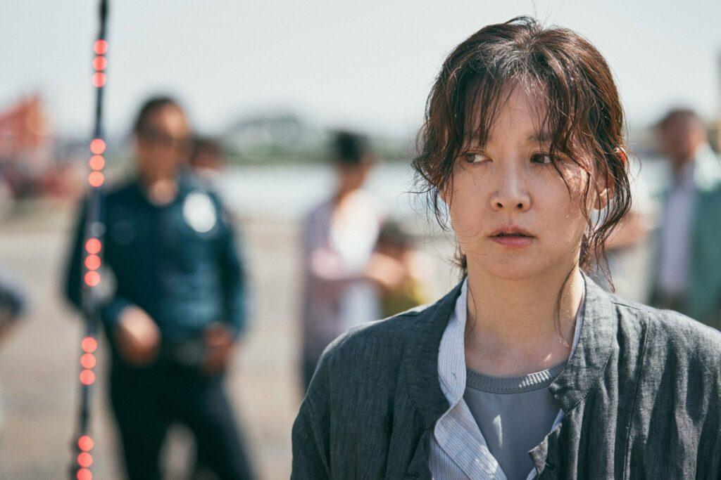 Die Hauptdarstellerin aus Bring Me Home schaut verunsichert zur Seite, während im Hintergrund weitere Personen stehen