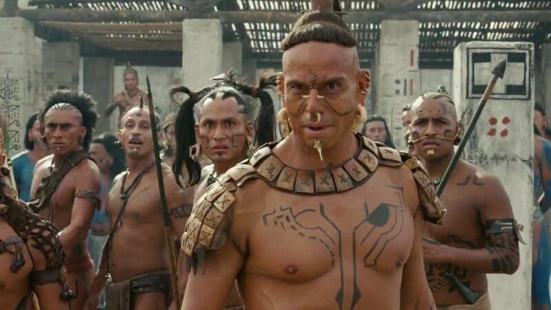 Einige Maya-Krieger stehen aufgereiht und kampfbereit nebeneinander, ihr Anführer starrt entschlossen Richtung Kamera