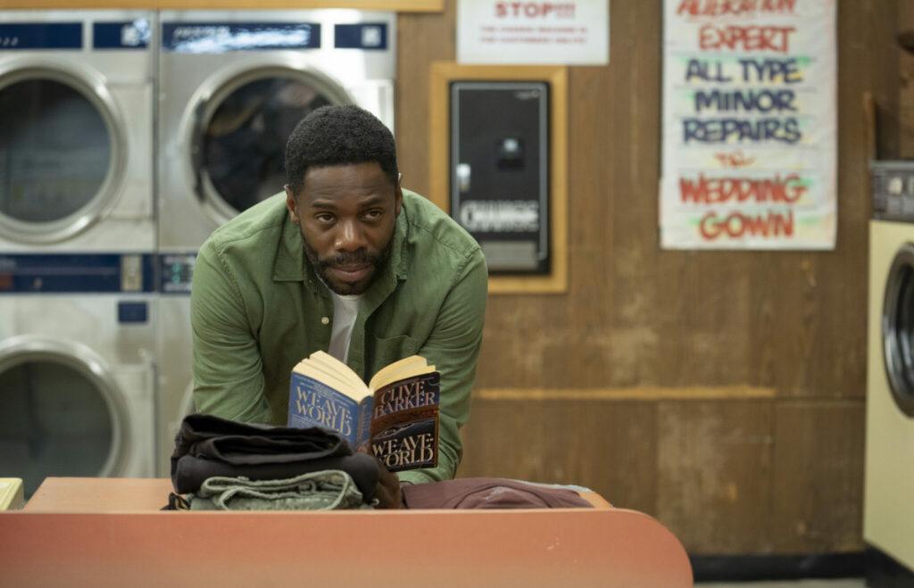Ein Mann steht mit einem Buch von Clive Barker in einem Waschsalon in Candyman