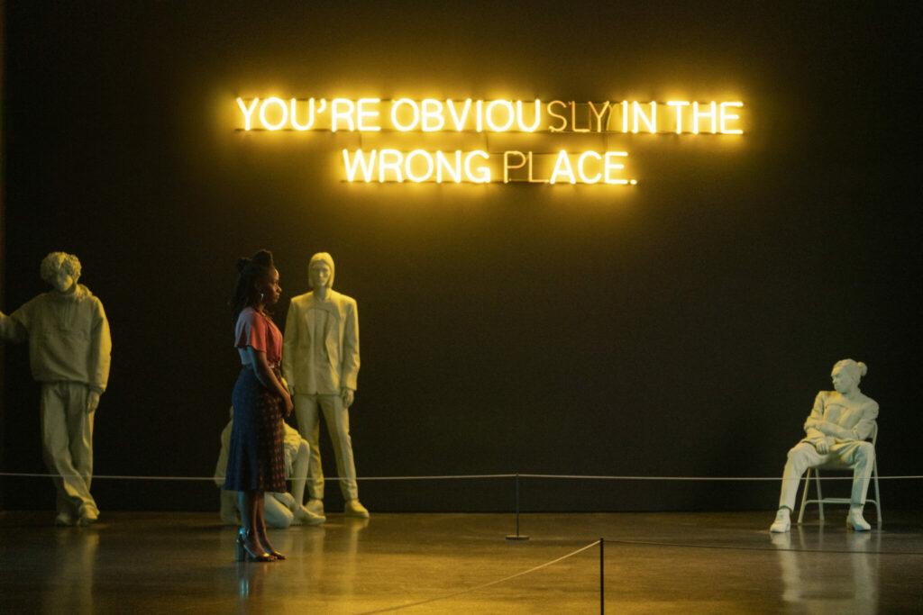 """Brianna steht in ihrer Galerie und im Hintergrund sieht man """"You're obvously in the wrong place"""" an der Wand."""