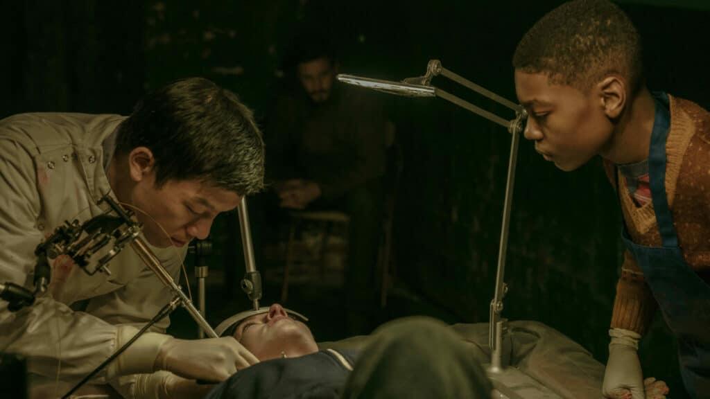 Gabriel Drummond, gespielt von Ashton Sanders, schaut zu, wie ein Untergrundarzt einem Rebellen die implantierte Überwachungswanze entfernt.