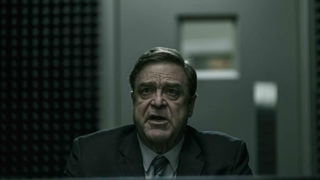 Detective Mulligan, gespielt von John Goodman, sitzt in einem Verhörraum.