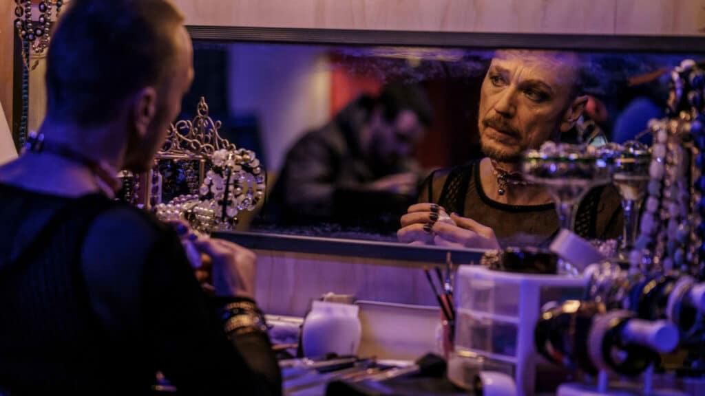 Ben Daniels spielt in Captive State den Rebellen Daniel, der sich vor einem Spiegel schminkt und sich auf das Attentat vorbereitet.
