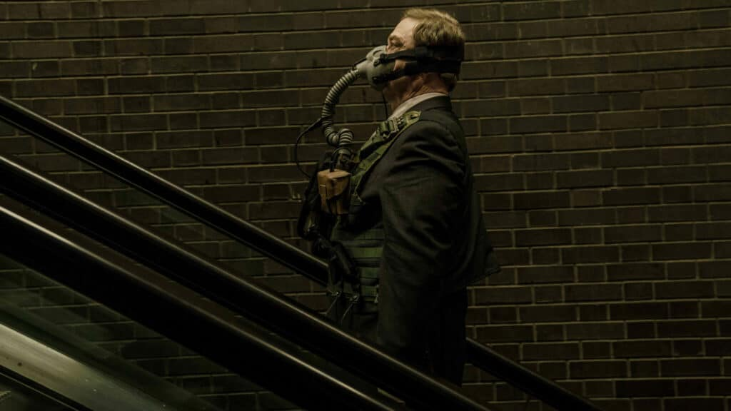 Ausgerüstet mit einem schweren Atemschutzgerät fährt Mulligan, gespielt von John Goodman, in Captive State eine Rolltreppe hinauf.