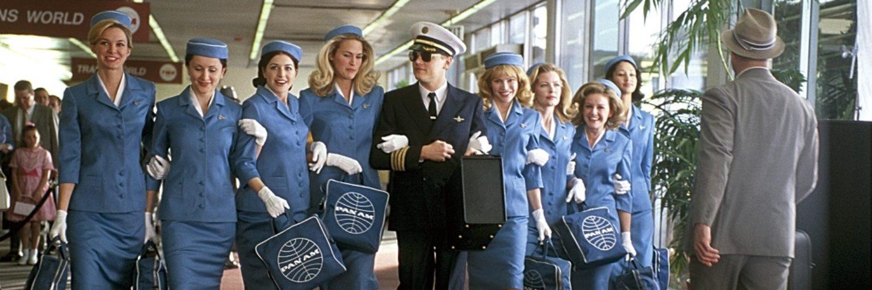 Leonardo DiCaprio läuft als Frank Abagnale im Piloten-Outfit mit acht Stewardessen in blauem Dress einen Gang im Flughafen entlang.