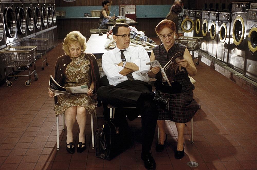 FBI-Agent Hanratty (Tom Hanks) sitzt mit verschränkten Armen in einem Waschsalon zwischen zwei alten Damen in Catch Me If You Can.