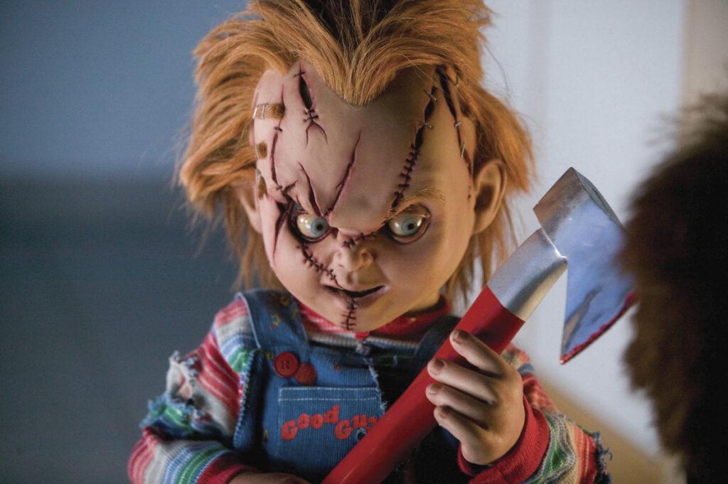 Chucky ist in einer Nahaufnahme zu sehen und hält eine Axt in der Hand. Auf der rechten Seite sieht man einen Teil der Silhouette eines Kopfes.