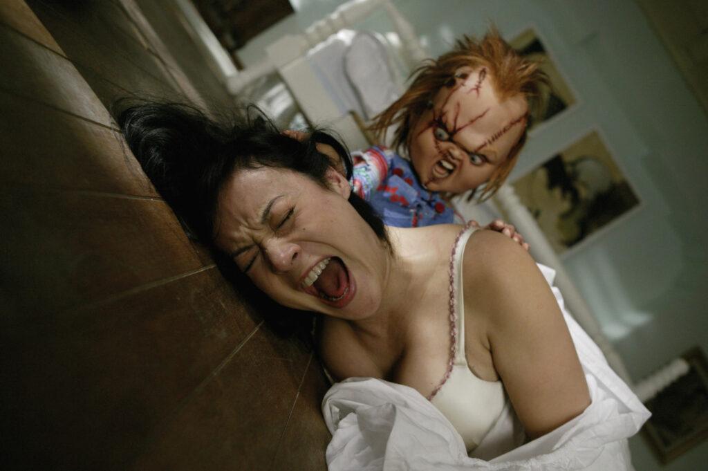 Tiffany liegt in diagonaler Perspektive im Brautkleid auf dem Boden und schreit. Hinter ihr trachtet ein grimmig dreinblickender Chucky nach ihr.
