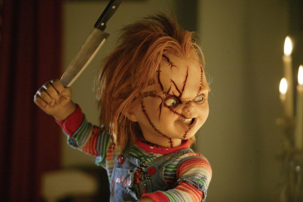 Chucky blickt nach rechts und hält die Spitze eines Messers in der rechten Wurfhand.
