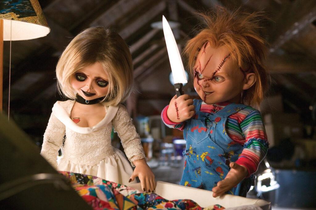 Tiffany steht auf der linken Seite des Bildes und blickt nach unten. Chucky steht rechts neben ihr und blickt auf das Messer, dass er in seiner rechten Hand vor dem Gesicht hält.