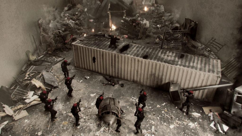 Will Bowman, gwespielt von Josh Holloway, sitzt nach einem Bombenanschlag auf dem zerstörten Kastcontainer, von Rothüten mit Gewehren bedroht.