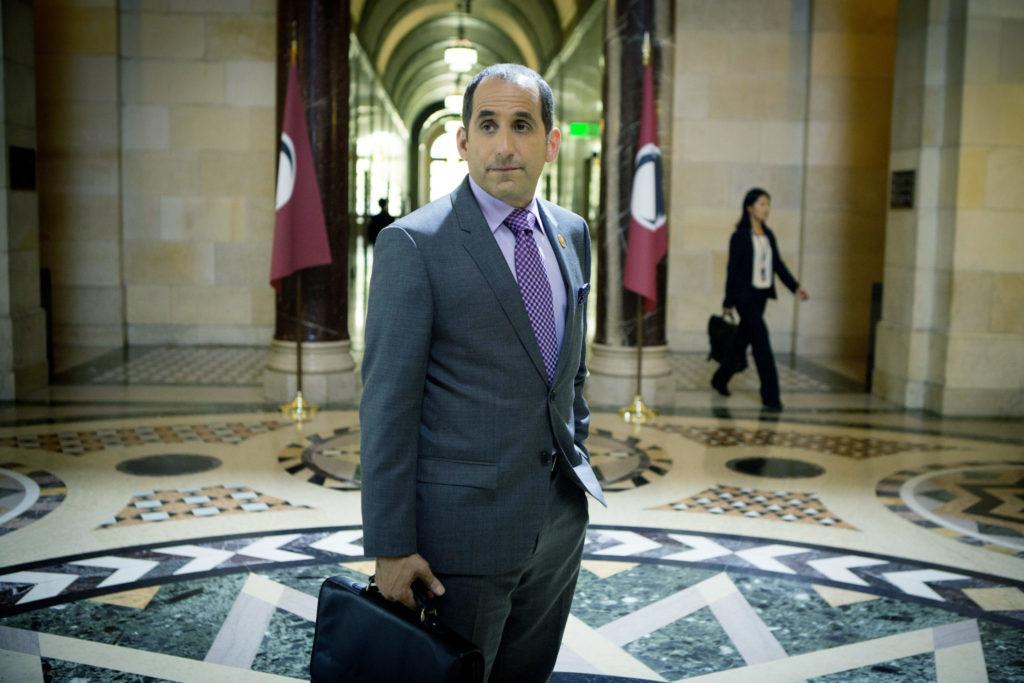 Proxy Alan Snyder, gespielt von Peter Jacobson, steht in Colony - Staffel 1 mit Aktentasche im Foyer des Regierungsgebäudes.