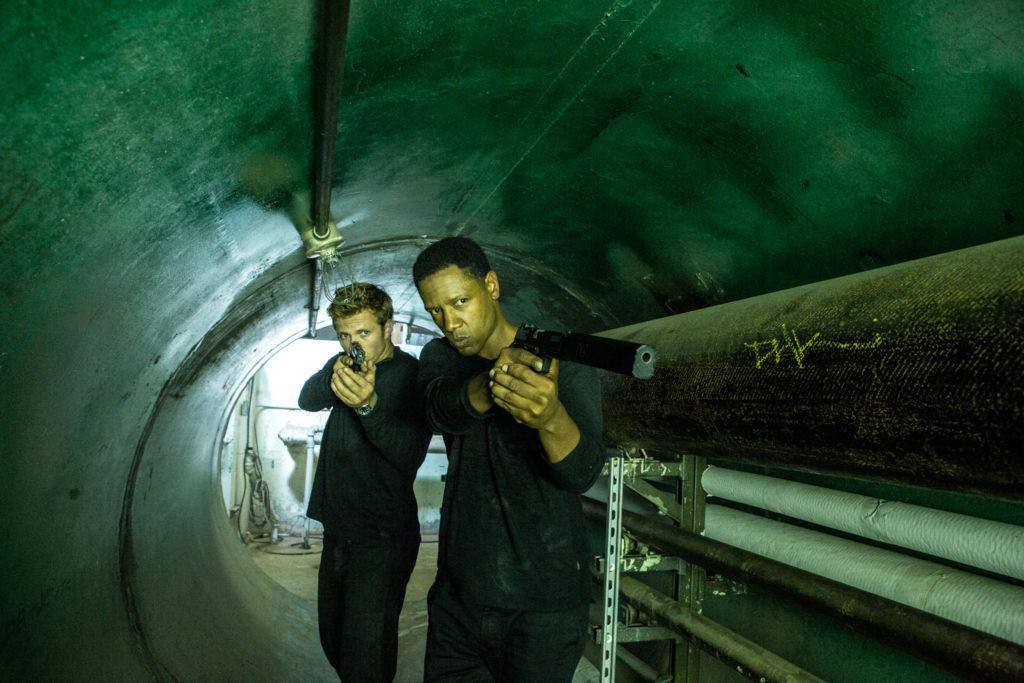Widerstandskämpfer Broussard, gespielt von Tory Kittles, und eine Kumpan gehen mit den Waffen im Anschlag durch einen Tunnel.
