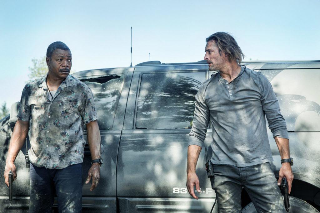 Will Bowman, gespielt von Josh Holloway, und sein von Carl Weathers gespielter Partner stehen an einem Auto.