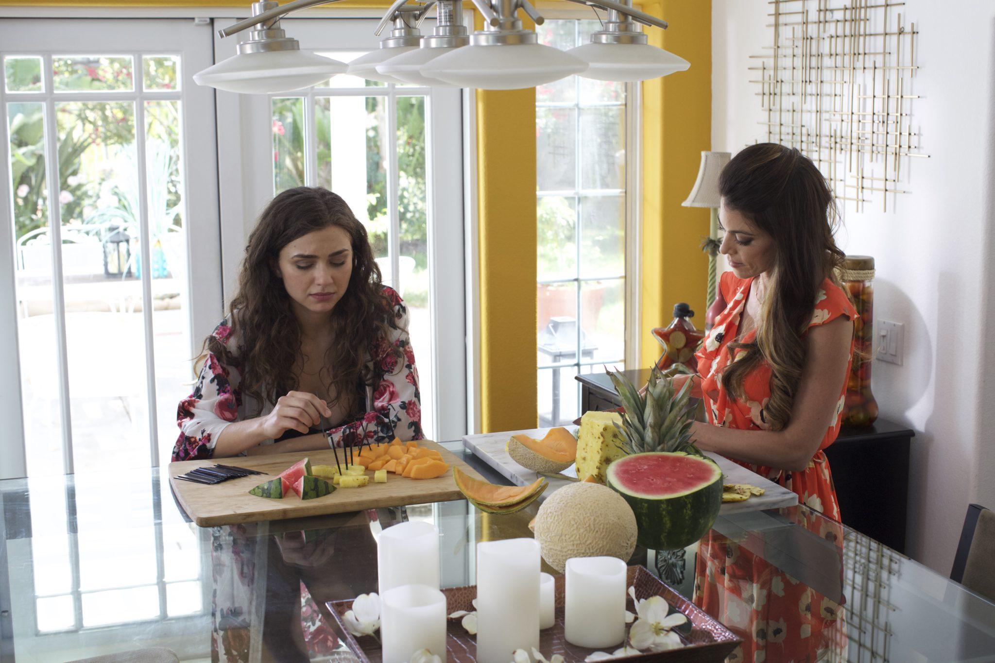 Lindsey Hartley als Mutter Lindsey und Victora Konefal als ihre Tochter sind zu sehen, wie sie Melonen zum Frühstück verspeisen.
