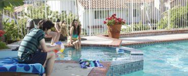 Mehrere leicht bekleidete junge Leute sind an einem Pool zu sehen.