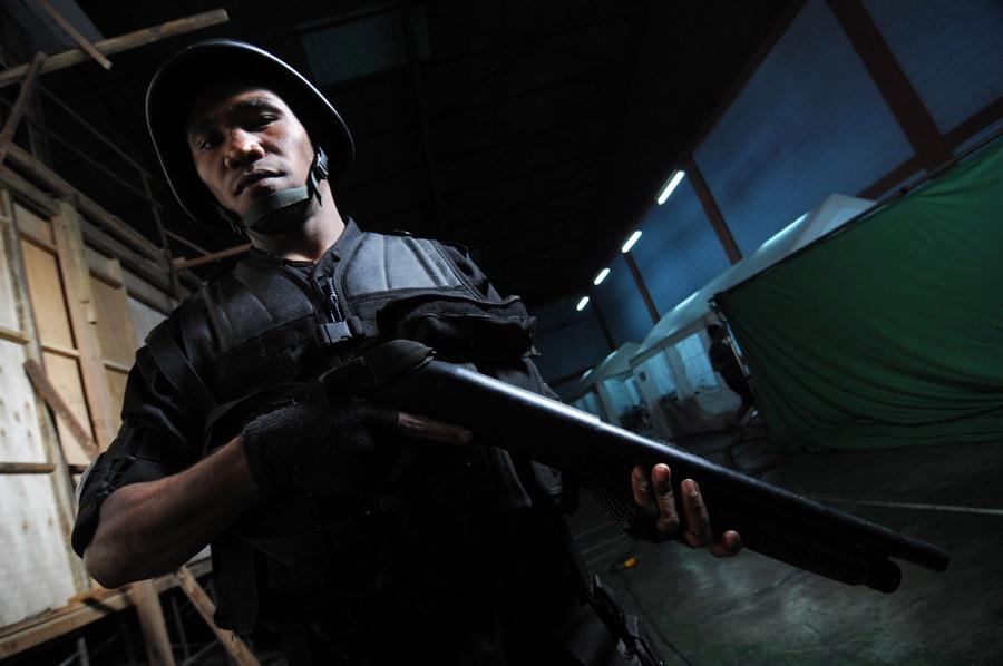 Ein SWAT-Einsatzmitglied mit gezückter Schrotflinte, Helm und Schutzweste