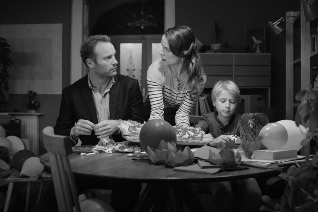 Matthias und Lukas sitzen am Tisch, Anna steht dahinter und schaut Matthias mit leerem Gesichtsausdruck an.