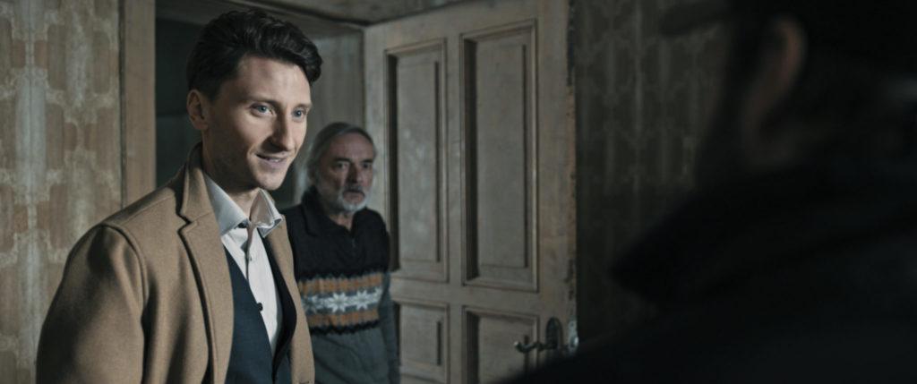 Der Makler (Moritz Heidelbach) und der namensgebende letzte Mieter (Wolfgang Packhäuser) stehen im Hausflur vor einer geöffneten Tür