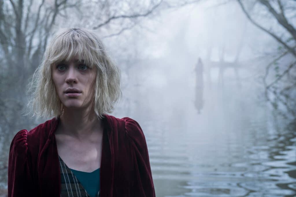 Mackenzie Davis steht mit ihrem Rücken zu einem See, eine Geistererscheinung im Hintergrund in Die Besessenen
