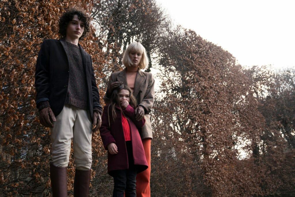 Die Hauptdarsteller Finn Wolfhard, Mackenzie Davis und Brooklyn Prince stehen nebeneinander im Park in Die Besessenen