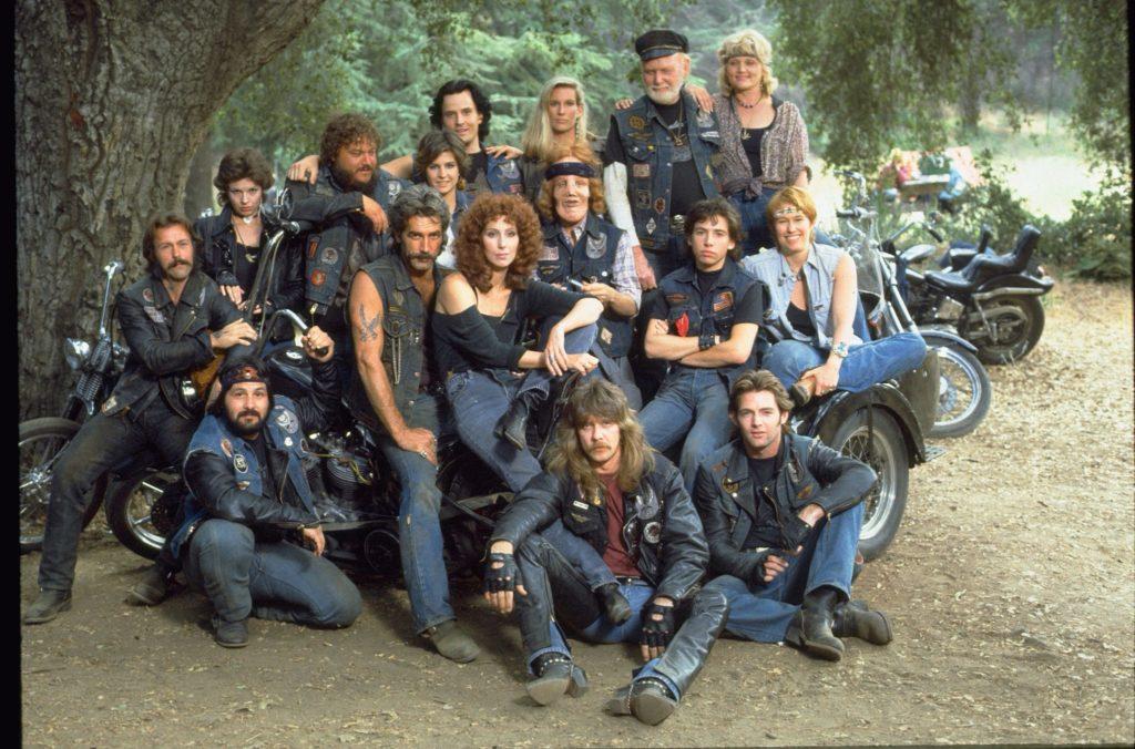 Ein Gruppenbild mit allen Bikern und den Hauptfiguren stehen und sitzend auf den Motorrädern in Die Maske