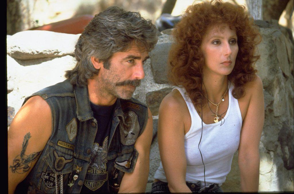 Cher als Rusty und Sam Elliott als Gar sitzen gemeinsam nebeneinander auf einem Stein in Die Maske