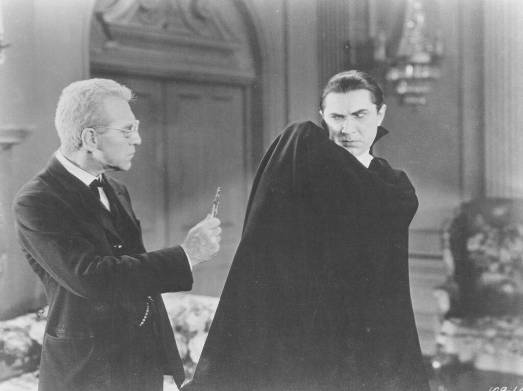 Graf Dracula zuckt beim Anblick des Kreuzes zusammen, das Van Helsing ihm entgegenstreckt - Universal Horror Filme
