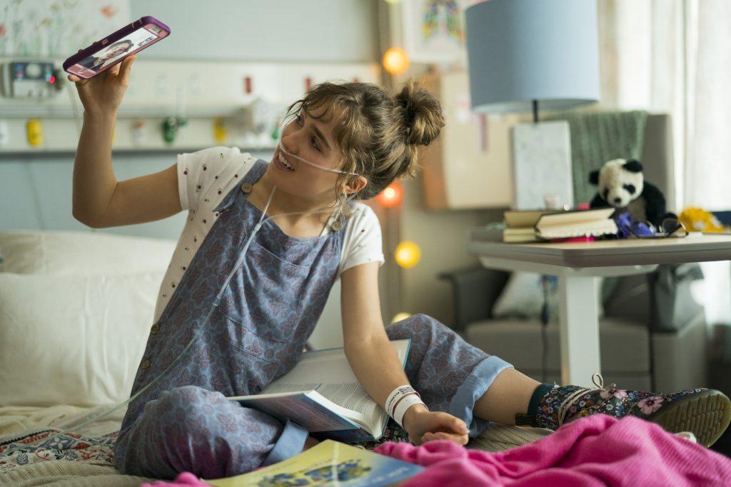 Haley Lu Richardson als Stella in Drei Schritte zu dir sitzt auf ihrem Krankenhausbett und telefoniert mit ihrem Handy mit Will