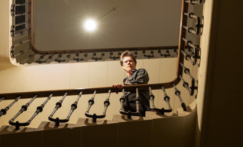 Theo (K_evin Bacon) schaut vom Treppengeländer hinab in die Geheimnisse des Hauses