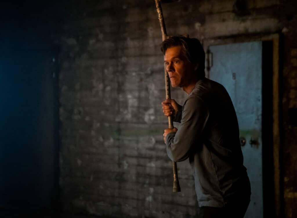 Theo (Kevin Bacon) setzt sich in einem dunklen Raum mit einem Stock zur Wehr.