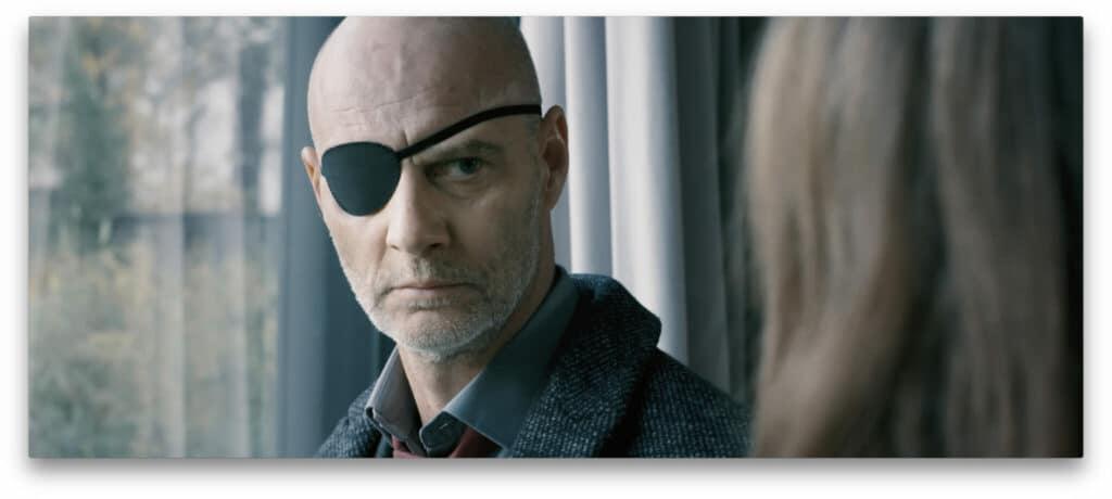 Simon Licht als Kommissar Alexander Bischof mit einer Augenklappe schaut zu seiner Chefin in Dünnes Blut