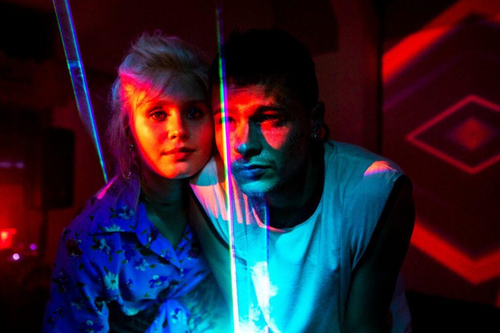 Milla und Moses stehen im Neon-Licht auf einer Party und sehen Richtung Kamera