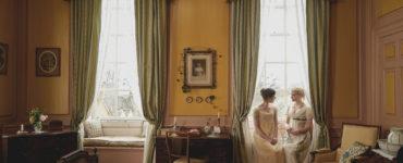 Emma, gespielt von Anya Taylor-Joy, und Harriet, gespielt von Mia Goth, sitzen am rechten Bildrand auf der Fensterbank von Emmas Schlafzimmer.