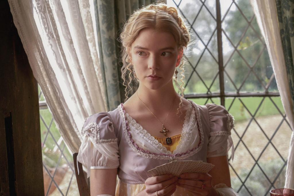 Emma, gespielt von Anya Taylor-Joy, sitzt vor einem Fenster und hält ein Blatt Spielkarten in den Händen.