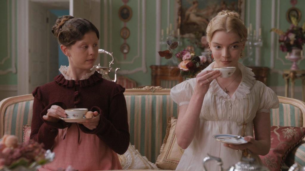 Emma, gespielt von Anya Taylor-Joy, und Harriet, gespielt von Mia Goth, sitzen auf einem Sofa und trinken Tee. Harriet beobachtet Emma, um die korrekte Haltung zu lernen.