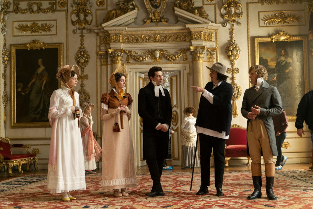Elton, gespielt von Josh O-Connor steht in der Mitte des Freundeskreises, mit dem er das Schloss von Mr. Knightley, gespielt von Johnny Flynn, besichtigt. Knightley steht rechts. Die Gruppe steht in einem Prunksaal voller Gemälde.