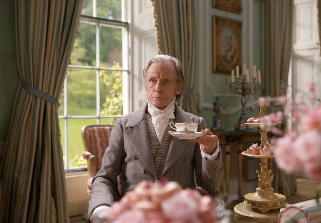Emmas Vater, gespielt von Bill Nighy, sitzt vor einem Fenster. In der erhobenen linken Hand hält er eine Tasse mit Tee.