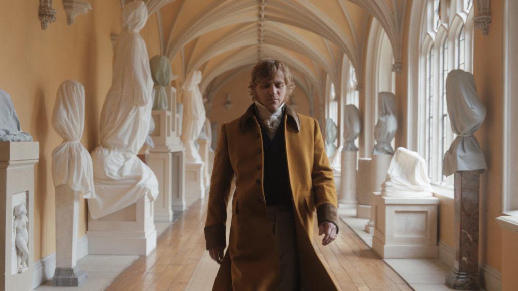 George Knightley, gespielt von Johnny Flynn, läuft durch einen säulenbestandenen Flur seines Schlosses. Die Bildkomposition ist betont symmetrisch.