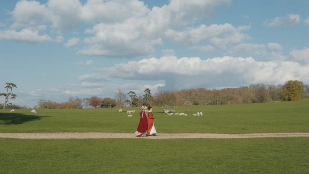 Emma, gespielt von Anya Taylor-Joy, und Harriet, gespielt von Mia Goth, laufen auf einem Weg an Wiesen vorbei, auf denen Schafe weiden.