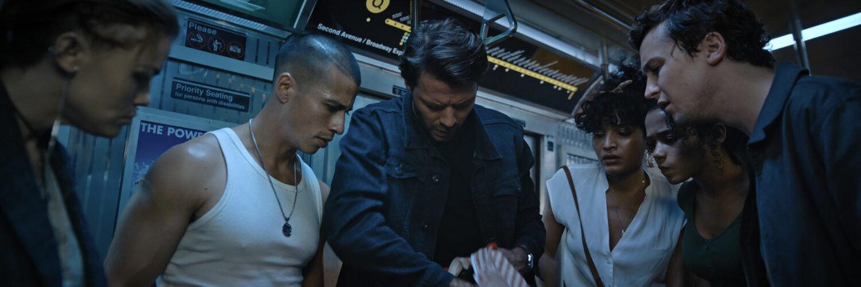 Die Protagonisten durchsuchen eine Tasche in einem U-Bahn-Waggon in Escape Room 2: No Way Out